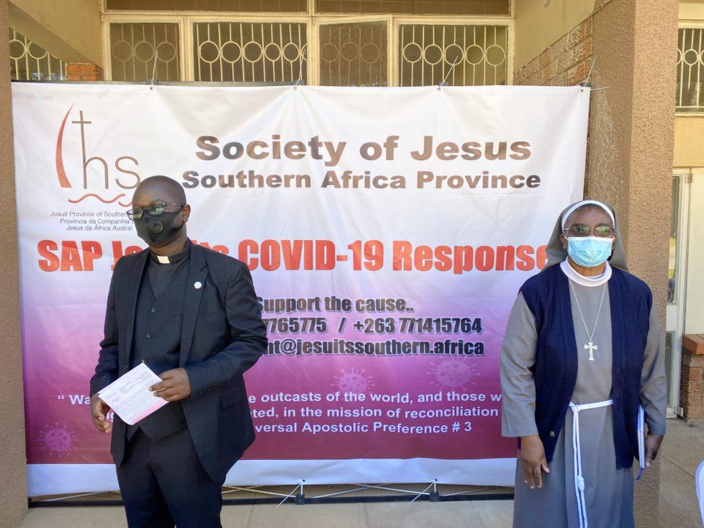 (Left-to-Right:) Pe. Nicholas Penge SJ, Delegado do SAP para a Zâmbia, com Ir. Agnes Lungu, Coordenadora Nacional de Saúde na Conferência Zambiana de Bispos Católicos, representando o Bispo George Lungu, Bispo da Diocese de Chipata, na entrega de pacotes de alimentos na Cúria Jesuíta em Lusaka, Zâmbia.